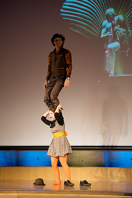 Photograph by Nicolas Sridi.  A woman with a man standing on her shoulders.
