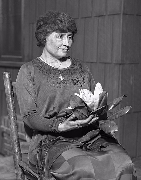 Helen Keller sitting, holding a magnolia flower, circa 1920. Image from the Los Angeles Times.
